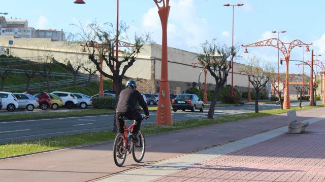 Un ciclista circula por el carril bici del paseo marítimo.