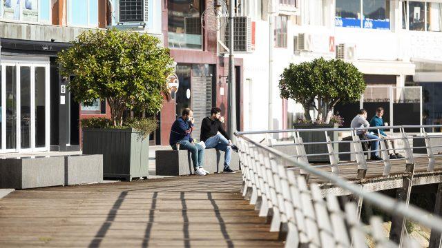 Dos personas permanecen sentadas en un banco de Sanxenxo
