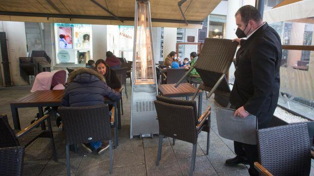 Un camarero recoge las sillas y mesas en un local de Lugo.