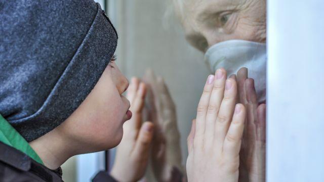 Una anciana ve a su nieto a través de una ventana en una foto de archivo.