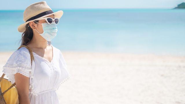 Una mujer camina por la playa con la mascarilla puesta.