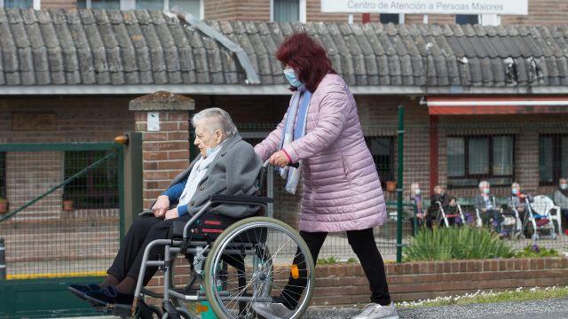 Una mujer pasea a una anciana en silla de ruedas, en las inmediaciones de la residencia geriátrica de As Gándaras (Lugo).