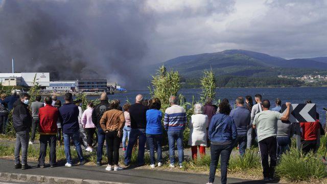 Numerosos vecinos observan el incendio de la conservera Jealsa, en Boiro (A Coruña).