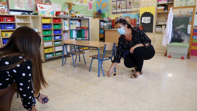 Dos profesoras miden la distancia entre pupitres.
