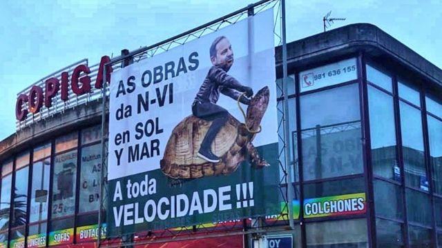 Cartel en Oleiros de la campaña contra la lentitud en las obras