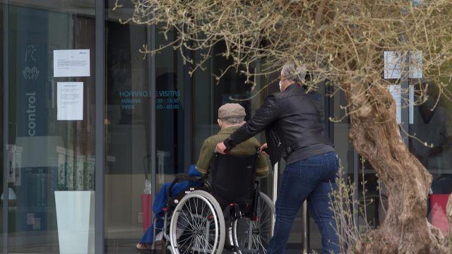 Una mujer pasea junto a un anciano en silla de ruedas.