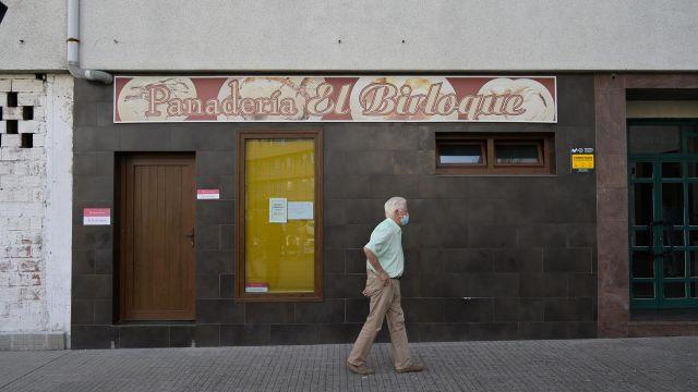 Un hombre pasa por delante de la Panadería El Birloque, regentada por la mujer asesinada en A Coruña.
