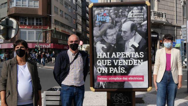 Representantes del BNG con el cartel publicitario colocado en A Coruña.