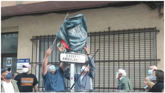Vecinos retirando el cobertor de la señal de reservado para ambulancias.