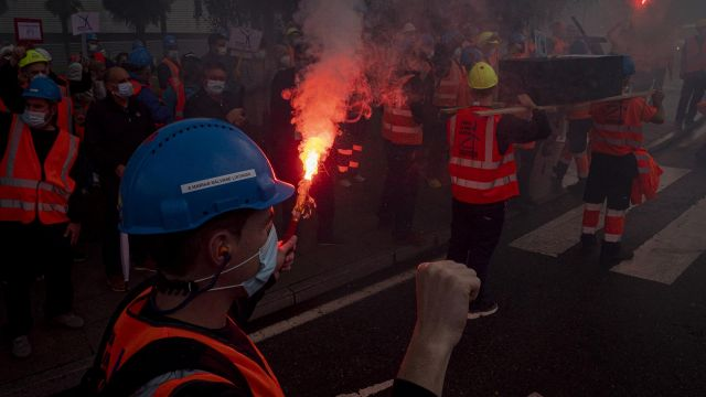 Un trabajador de Vestas enciende una bengala en una marcha contra el cierre de la fábrica de Viveiro (Lugo) realizada en Santiago de Compostela.