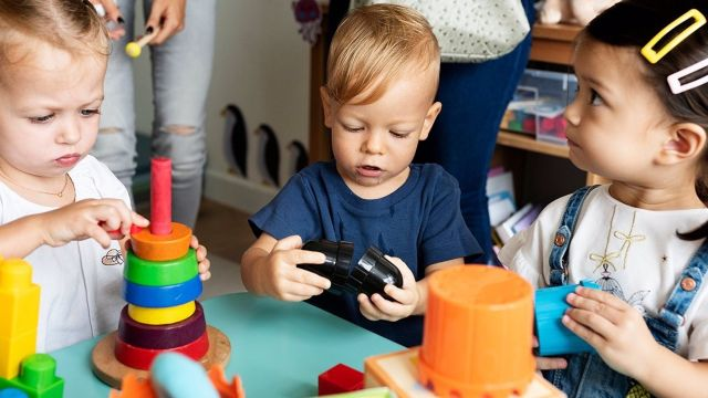 Varios pequeños juegan en una guardería.